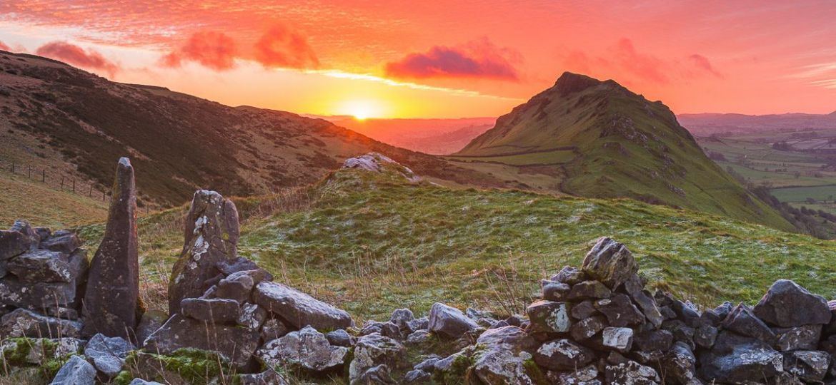 The sun rises over the horizon looking across towards Chrome Hill in the Peak District