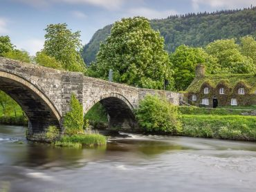 An elegant 17th century stone bridge over the River Conwy at Llanrwst, with the ivy-clad Tu Hwnt ir Bont National Trust tearooms on the western side. The bridge was built in 1636
