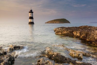 Puffin Island and Trwyn Du Lighthouse near Penmon in Anglesey North Wales with the sunset light taken in July 2013