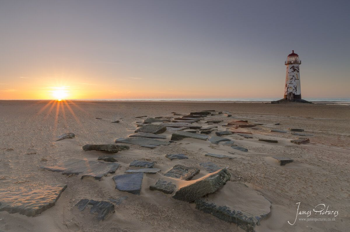 The sun setting on Talacre Beach with Talacre Lighthouse in the middle distance