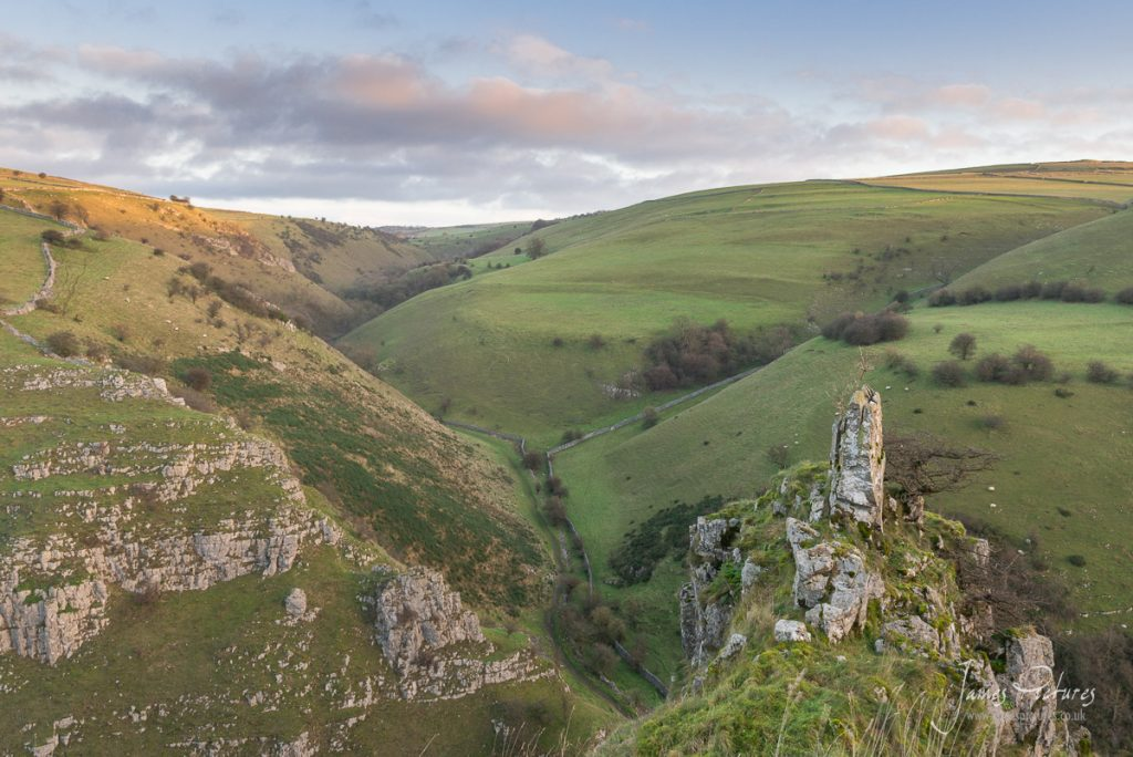 The morning sun hits the top of Biggin Dale in the Peak District. And a 7ft Limestone Pinnacle dominates the foreground.