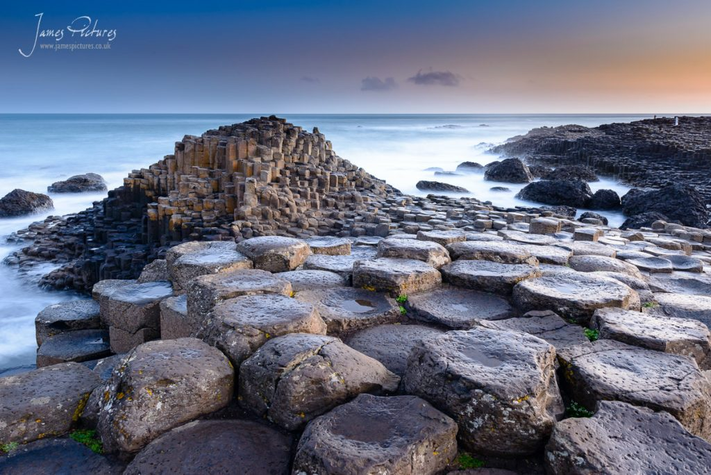 The stunning Giants Causeway in County Antrim, Northern Ireland at sunrise. a stunning creation of over 40,000 interlocking basalt columns, the result of an ancient volcanic eruption to admire.